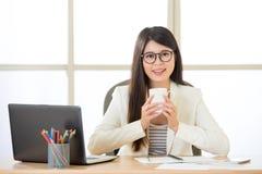 微笑和喝在膝上型计算机的愉快的亚裔女商人咖啡 库存图片