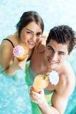 微笑和喝在水池的夫妇的画象一个鸡尾酒 库存照片