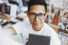 微笑和在手上的年轻atrractive戴了眼镜人拿着书 免版税图库摄影