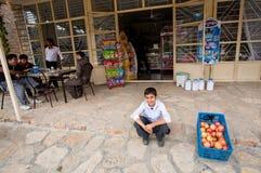 微笑和坐通过果子商店和咖啡馆的男孩在小村庄 免版税库存照片