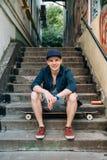 微笑和基于他的滑板的年轻溜冰板者人户外 灰色台阶和街道画在墙壁上在背景 库存图片