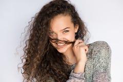 微笑和愉快的少妇看与卷发的一边 免版税图库摄影