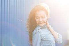 微笑和愉快的少妇看与卷发的一边 免版税库存照片