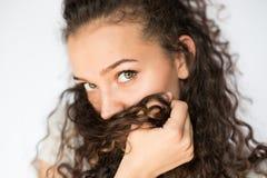 微笑和愉快的少妇看与卷发的一边 库存图片