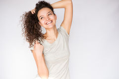 微笑和愉快的少妇看与卷发的一边 免版税库存图片