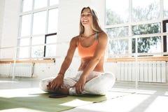 微笑和愉快的运动的妇女佩带的sportwear坐在晴朗的健身房的瑜伽席子在她前面是有健身的app一个智能手机 免版税库存照片