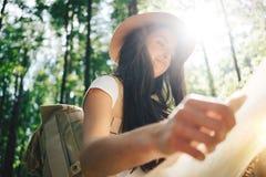 微笑和愉快的逗人喜爱的旅客妇女佩带的背包和帽子在手上拿着定位图在树中在日落 免版税库存照片