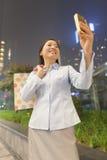 微笑和拍照片的她自己的年轻女实业家与她的手机 库存照片