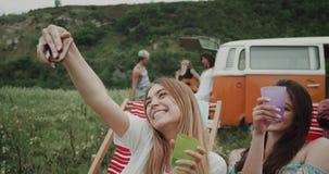微笑和拍照片的特写镜头两吸引人夫人在野餐,拿着五颜六色的玻璃,背景一些  股票视频