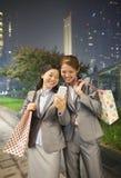 微笑和拍照片的他们自己的两名年轻女实业家与手机 免版税库存照片