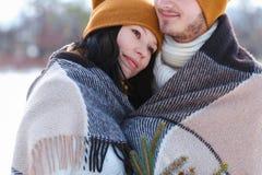 微笑和拥抱在backgr的冬天的年轻夫妇画象  库存图片