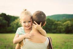 微笑和拥抱她的母亲的可爱的女孩 免版税库存图片
