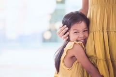 微笑和拥抱她的母亲腿的逗人喜爱的亚裔儿童女孩 免版税库存图片