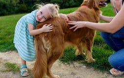 微笑和拥抱她逗人喜爱的爱犬的可爱的矮小的白肤金发的女孩 图库摄影