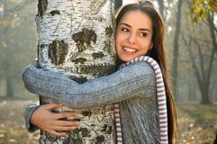 微笑和拥抱桦树的妇女 免版税库存图片