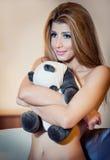 微笑和拥抱熊猫玩具的年轻白肤金发的肉欲的妇女。没有放松在她的屋子里的衣裳的美丽的女孩 免版税库存图片