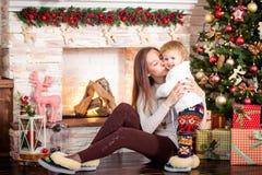 微笑和拥抱,摆在照相机的妈妈和女儿在新的Ye 免版税图库摄影