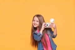 微笑和拿着一台减速火箭的照相机的小女孩摄影师 免版税库存照片