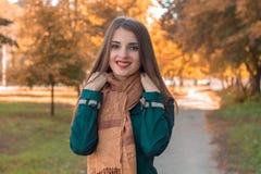 微笑和拿着一条围巾用您的手的美丽的女孩 免版税库存图片