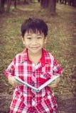 微笑和拿着书的亚裔男孩 登记概念教育查出的老 葡萄酒 免版税库存照片