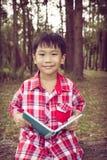 微笑和拿着书的亚裔男孩 登记概念教育查出的老 葡萄酒 免版税库存图片