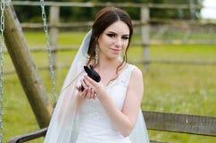 微笑和拿着在公园夏天自然的少妇新娘逗人喜爱的兔子室外 白色婚礼礼服,绿色背景 库存图片