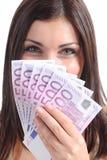 微笑和拿着很多五百张欧洲钞票的美丽的妇女 免版税库存照片