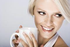 微笑和拿着杯子的美丽的白肤金发的妇女 免版税库存照片