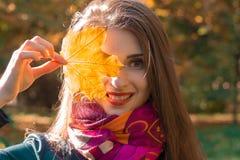 微笑和拿着橙色叶子的迷人的女孩在眼睛特写镜头附近 库存照片
