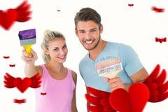 微笑和拿着油漆刷的年轻夫妇的综合图象 库存照片
