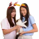 微笑和拿着猫阅读的两个年轻愉快的亚裔十几岁的女孩 免版税库存图片