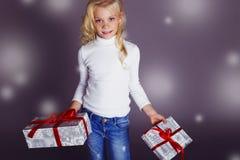 微笑和拿着礼物的美丽的小女孩牛仔裤 库存照片