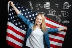 微笑和拿着美国的一面大旗子的爱国的妇女 免版税库存图片