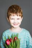 微笑和拿着花束的男孩 免版税库存照片