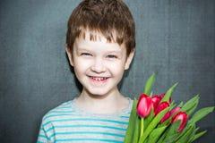 微笑和拿着郁金香的花束男孩。 库存图片