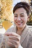 微笑和拿着黄色银杏树叶子的成熟妇女 免版税图库摄影