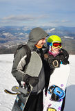微笑和拿着snowboads的女孩和男孩身分 免版税库存照片