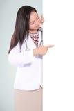 微笑和指向一个空白的委员会的美丽的妇女医生 库存照片