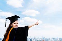 微笑和指向拷贝sp的毕业学术礼服或褂子的美丽的亚裔大学或大学毕业生学生妇女 免版税图库摄影