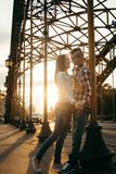微笑和握在日落的爱恋的夫妇的晴朗的情感射击手在铁拱道附近 库存图片
