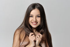微笑和握她的手的女孩对她的胸口 免版税库存照片