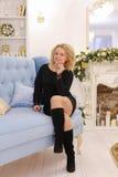 微笑和摆在坐长沙发的奇妙年轻白肤金发的妇女 免版税库存照片