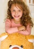 微笑和摆在她的玩具熊头的一个年轻俏丽的女孩的画象在医生办公室背景中 免版税库存照片