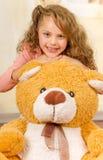微笑和摆在她的玩具熊s头的一个年轻俏丽的女孩的画象在医生办公室背景中 免版税库存照片