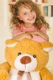 微笑和摆在她的玩具熊s头的一个年轻俏丽的女孩的画象在医生办公室背景中 免版税库存图片