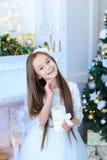 微笑和摆在照相机的女孩,举在背景的蜡烛 免版税库存照片