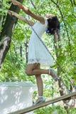 微笑和摇摆i的一件美丽的妇女白色礼服的画象 免版税库存图片