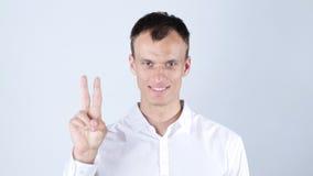 微笑和显示您在白色背景的年轻人画象胜利标志 库存图片