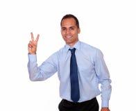 微笑和显示您胜利标志的迷人的人 免版税库存照片