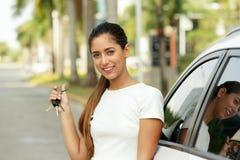 微笑和显示新的汽车的钥匙愉快的年轻成人 免版税库存照片